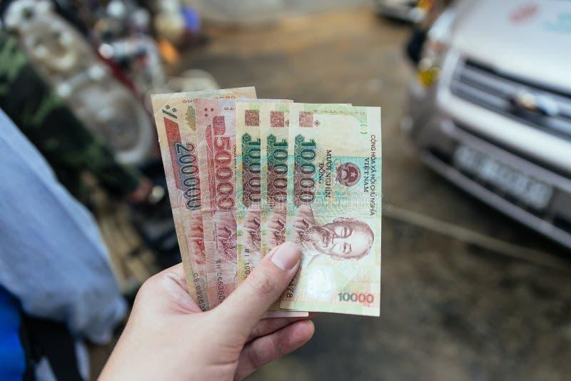 Cédulas vietnamianas no pagamento de espera da mão esquerda no Pa do Sa, Vietname foto de stock royalty free