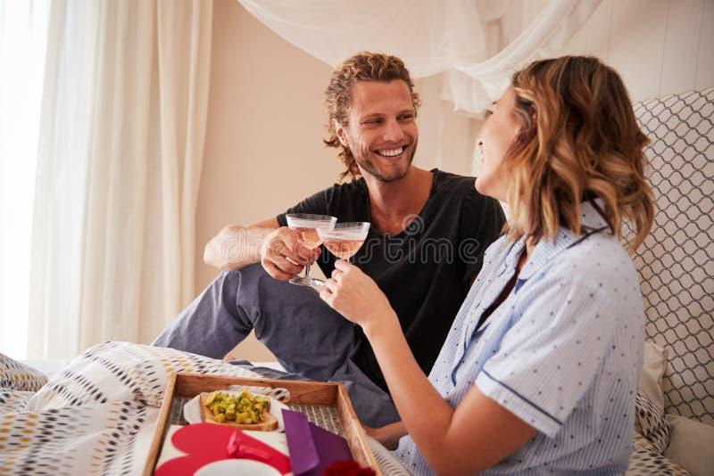 Célébration blanche millénaire de couples, faisant un pain grillé avec le champagne dans le lit, fin  photo stock