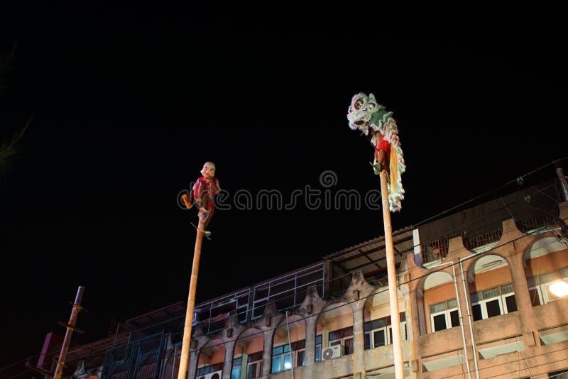 Célébration chinoise de nouvelle année par représentation traditionnelle de lion sur le dessus du poteau en bambou à la rue publi image stock