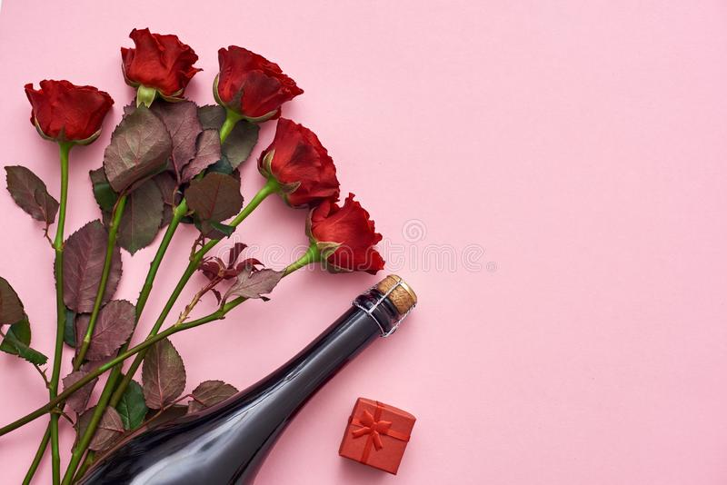 Célébration de la date spéciale Étonnez-la avec les roses rouges, le champagne et le petit boîte-cadeau rouge photos libres de droits