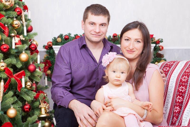 Célébration de Noël ou de nouvelle année Jeune famille heureuse s'asseyant dans la chaise près de l'arbre de Noël avec des cadeau photo stock