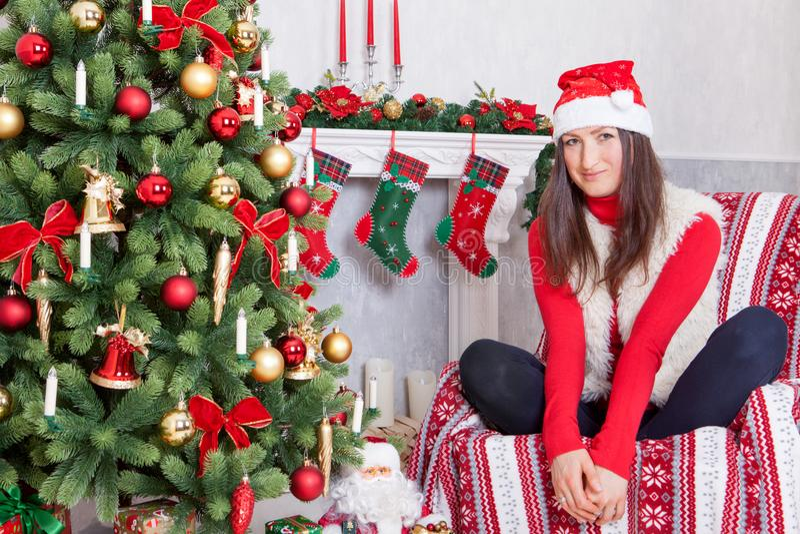 Célébration de Noël ou de nouvelle année La jeune femme dans un pullover rouge, gilet de fourrure et chapeau de Santa, s'assied d photos stock