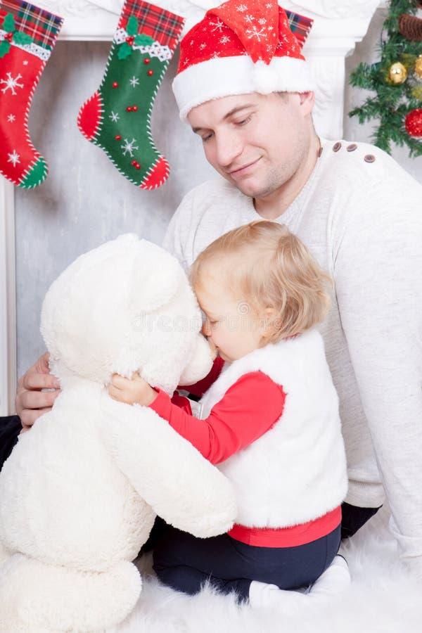 Célébration de Noël ou de nouvelle année Le père et la fille jouant avec le jouet soutiennent près de la cheminée de Noël avec le photo libre de droits