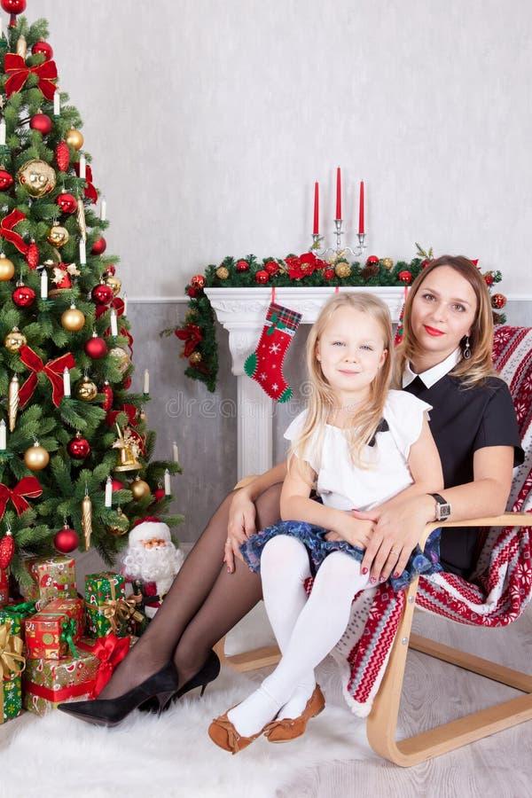 Célébration de Noël ou de nouvelle année Mère heureuse et fille s'asseyant dans la chaise près de l'arbre de Noël avec des cadeau photos libres de droits