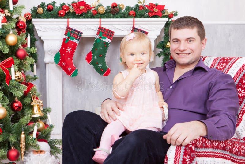 Célébration de Noël ou de nouvelle année Père heureux et fille s'asseyant dans la chaise près de l'arbre de Noël avec des cadeaux image stock