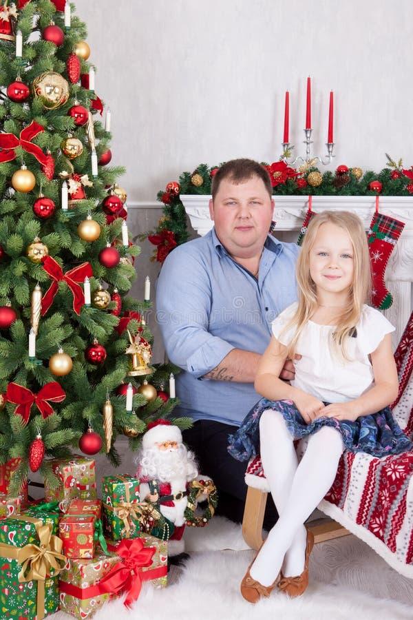 Célébration de Noël ou de nouvelle année Père heureux et fille s'asseyant dans la chaise près de l'arbre de Noël avec des cadeaux image libre de droits