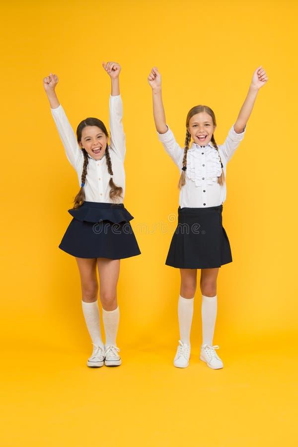 Célébration de nouveau à l'école Filles heureuses célébrant l'accomplissement dans l'étude sur le fond jaune Petits écoliers mign image libre de droits