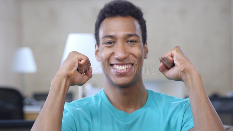 Célébration de succès par l'homme afro-américain chanceux dans le bureau, portrait images stock