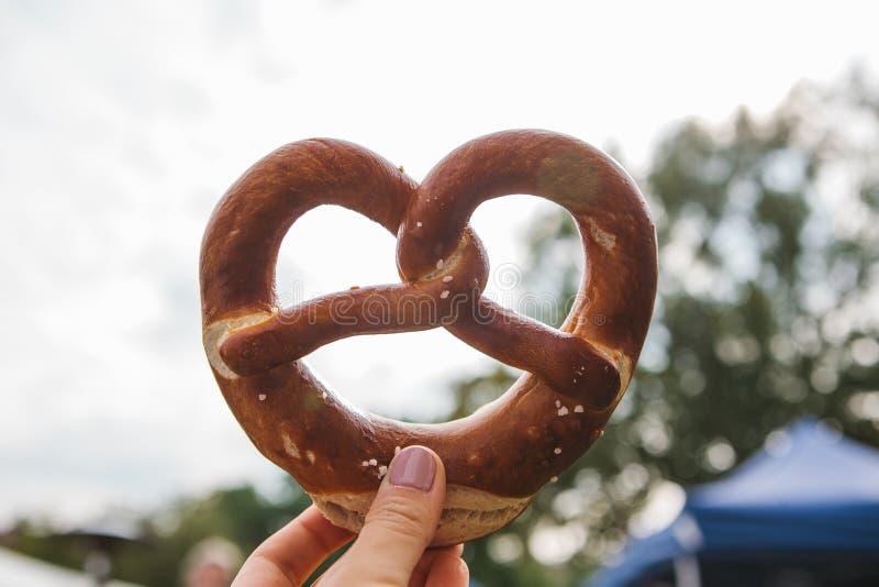 Célébration du festival allemand célèbre Oktoberfest de bière que la personne se tient dans sa main un bretzel traditionnel a app photos stock