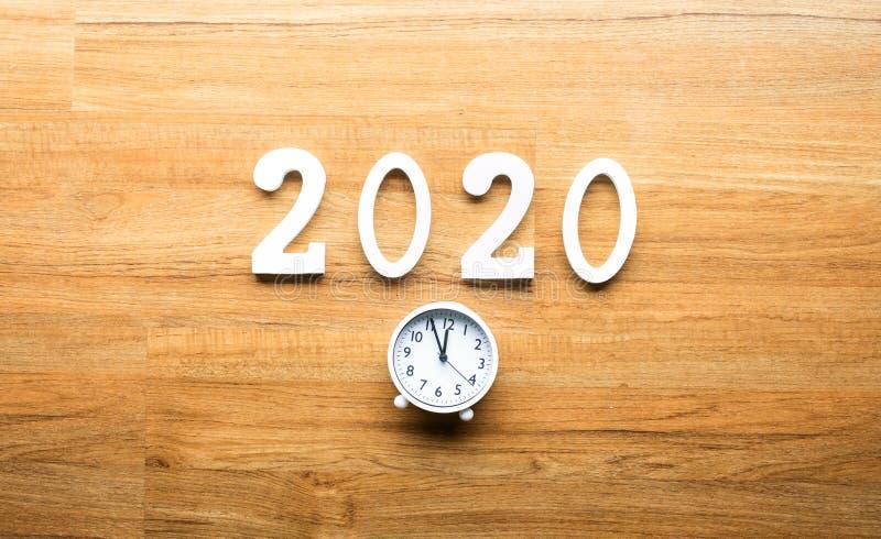 Célébration et compte à rebours des concepts de la nouvelle année 2020 avec le nombre des textes et réveil sur le fond en bois photographie stock libre de droits