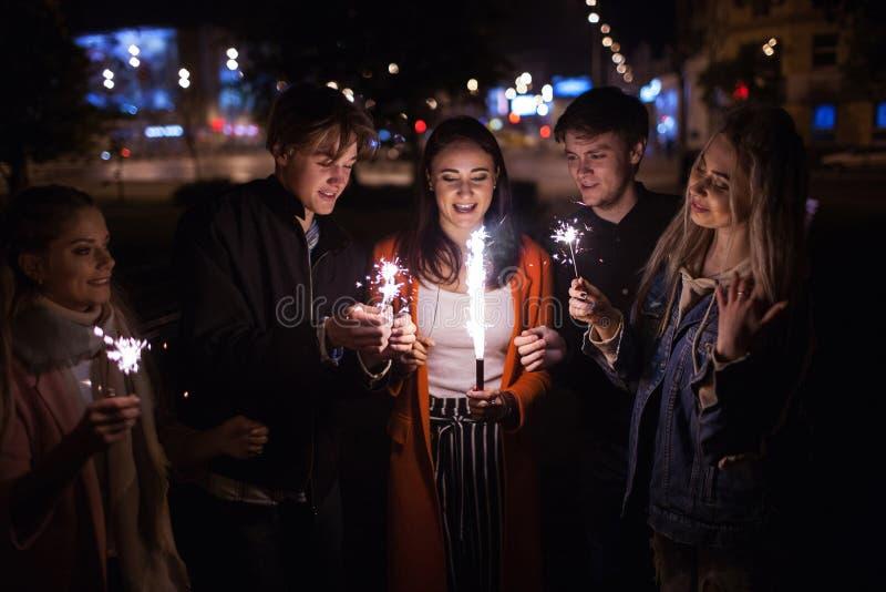 Célébration heureuse d'amis avec des cierges magiques dehors images stock
