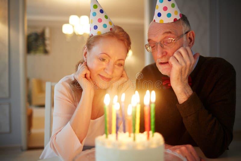 Célébration tranquille d'anniversaire des couples supérieurs affectueux images stock