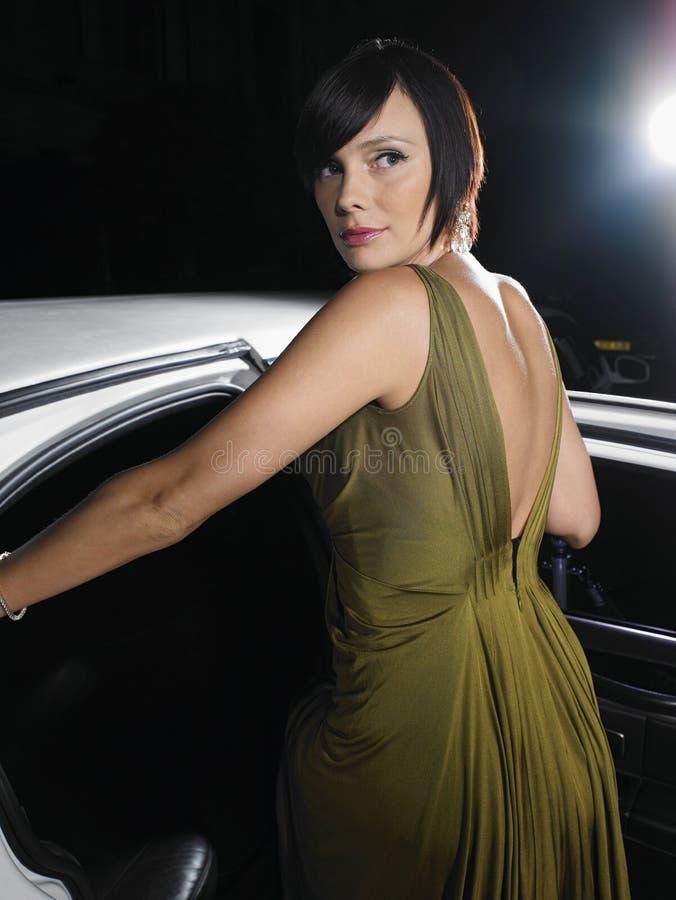 Célébrité dans l'usage de soirée entrant dans la limousine image stock
