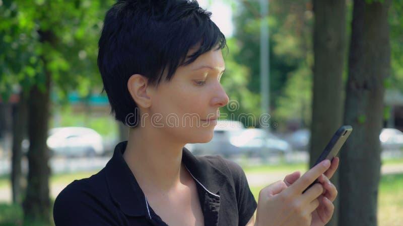 Célula del uso de la muchacha en el aire abierto foto de archivo libre de regalías