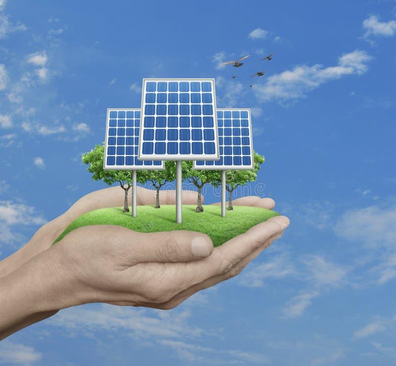 A célula solar com árvores e grama no homem cede o céu azul, whit imagem de stock
