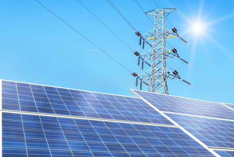 Células solares na energia alternativa de central elétrica do sol com as colunas elétricas de alta tensão do pilão imagem de stock