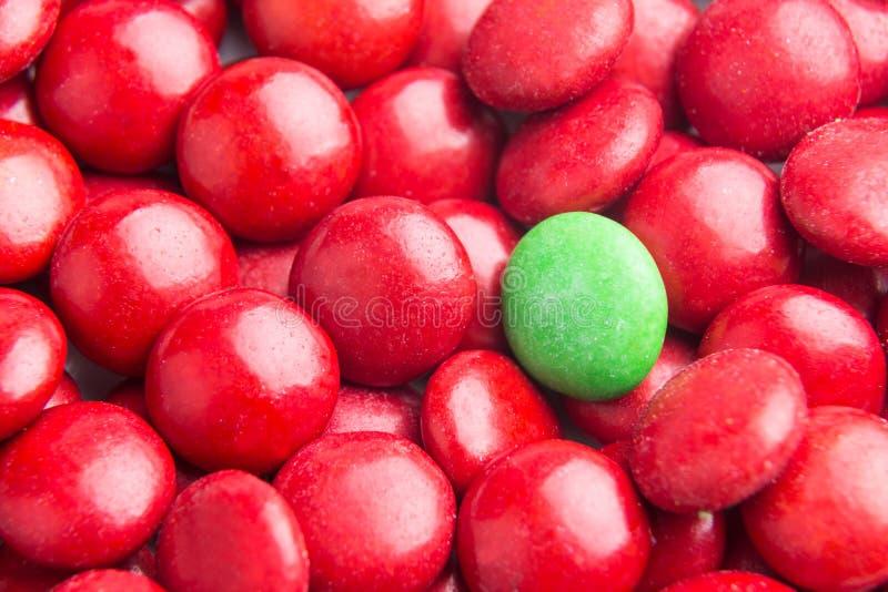 Céntrese en el caramelo de chocolate verde contra los montones de caramelos rojos imagenes de archivo