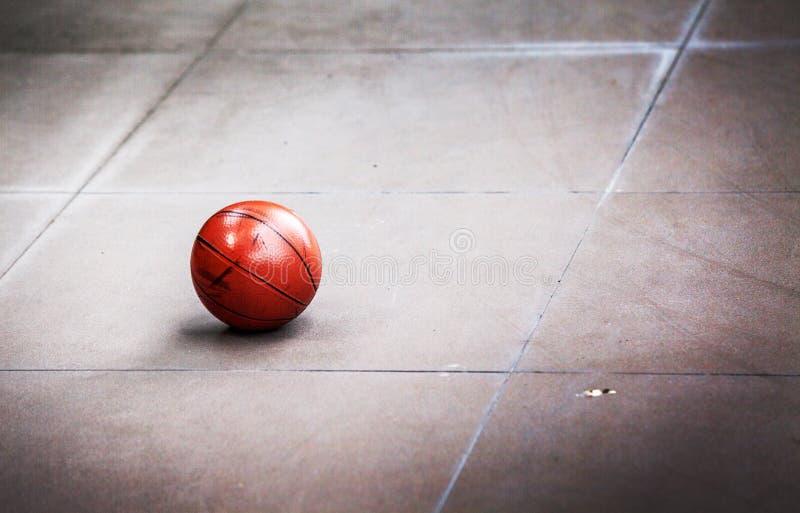 Céntrese la bola sucia de la cesta en el piso del cemento imagenes de archivo