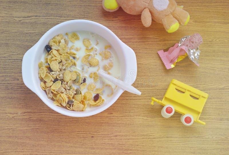 Céréales dans un bol blanc Jouets pour bébés Petites poupées Jouets de train Crackers Snacks Tableware Articles en bois Petit déj photographie stock libre de droits