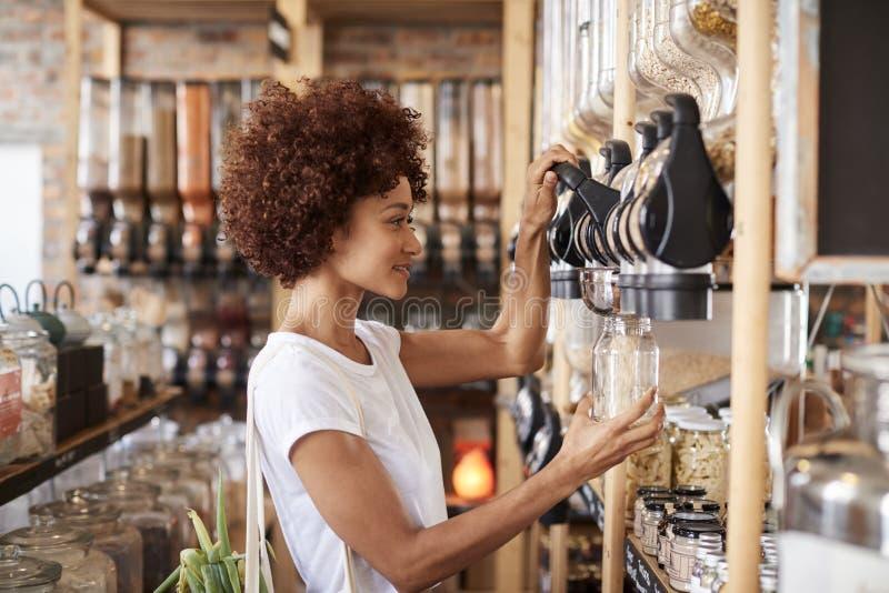 Céréales et grains d'achats de femme dans l'épicerie libre en plastique viable photos libres de droits