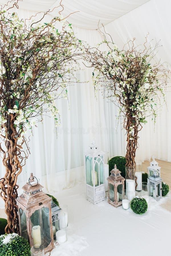 Cérémonie de mariage intérieure avec arche de mariage blanche décorée de fleurs et de grandes bougies blanches photo stock