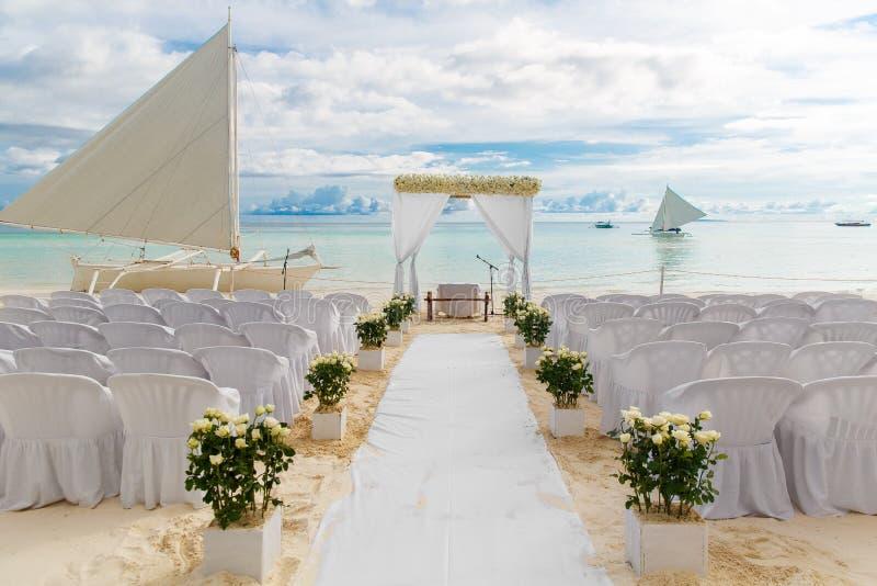 Cérémonie de mariage sur une plage tropicale dans le blanc La voûte est décor photo libre de droits