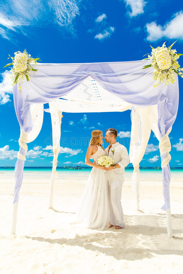 Cérémonie de mariage sur une plage tropicale dans le blanc Marié heureux et b photographie stock libre de droits