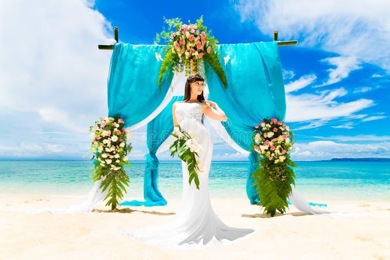 Cérémonie de mariage sur une plage tropicale Jeune mariée heureuse sous la voûte de mariage photographie stock libre de droits