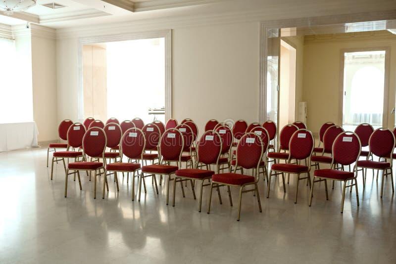 Cérémonie l'épousant dans le hall de banquet à l'intérieur Rangées des chaises pour des invités au mariage Une chaise en velours  photo libre de droits