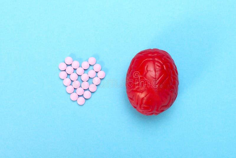 Cérebro vermelho em um fundo azul com comprimidos cor-de-rosa Alguns comprimidos para o c?rebro É simbólico para drogas fotos de stock