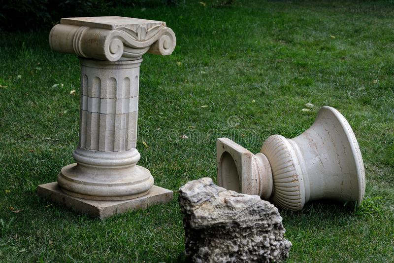 Césped con la hierba verde y las esculturas de mármol blancas, detalles del patio con arquitectura y plantas fotografía de archivo libre de regalías
