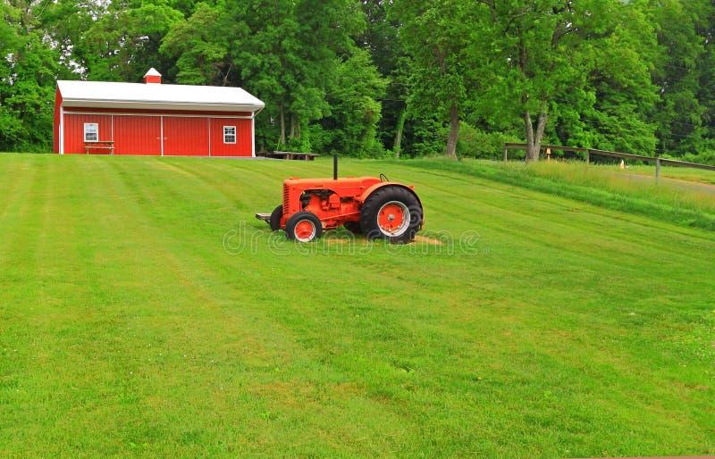 Césped rojo del verde del tractor del granero foto de archivo