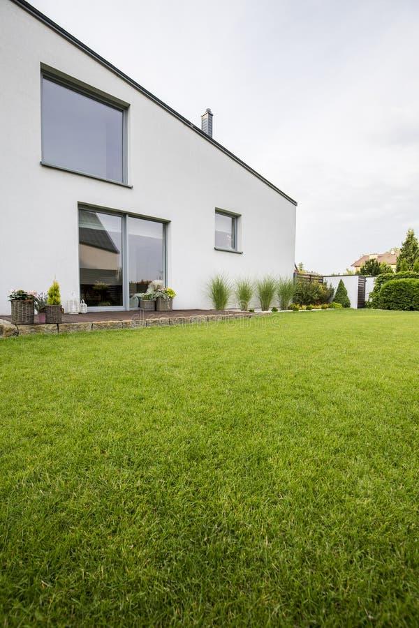 Césped verde hermoso en el patio trasero de un hou residencial moderno imagen de archivo