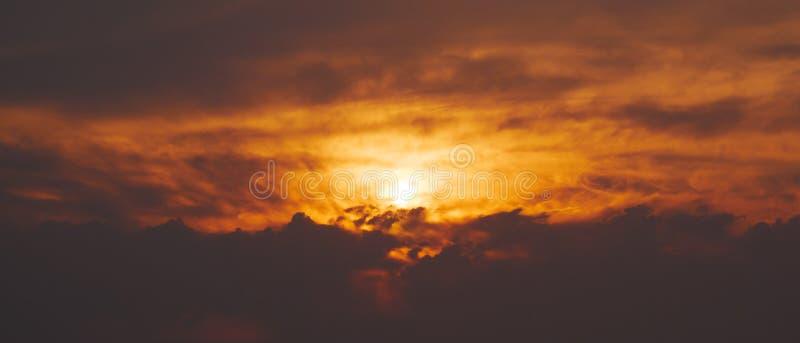 Céu alaranjado vívido do por do sol com as nuvens escuras, dramáticas fotos de stock