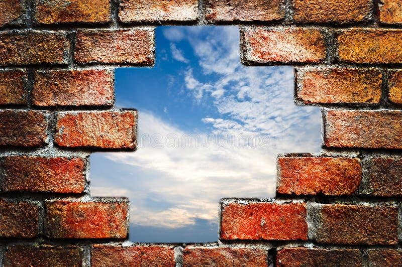 Céu azul através da parede de tijolo antiga fotografia de stock
