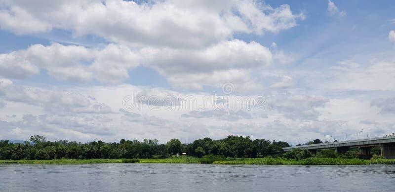 Céu azul bonito com estrada ou ponte através do rio pelo veículo, pelas nuvens brancas e pela árvore verde imagens de stock