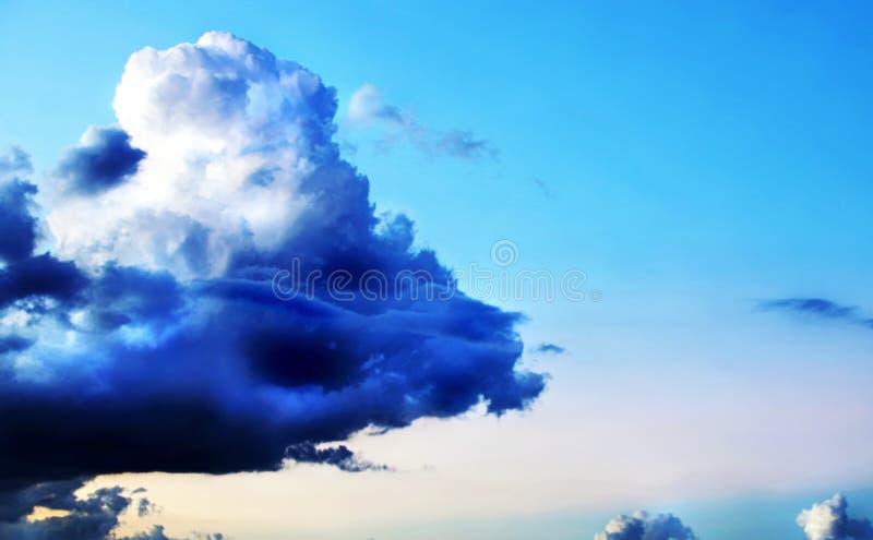 Céu azul brilhante do fundo com a uma nuvem de tempestade escura imagem de stock royalty free