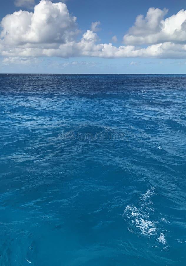 Céu azul claro sobre a água de cristal do oceano fotos de stock royalty free