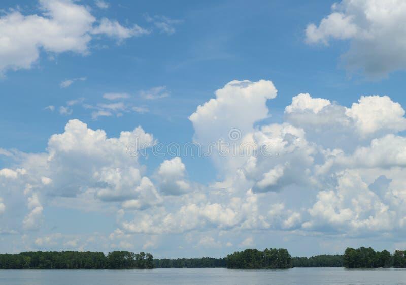 Céu azul com as nuvens inchados brancas sobre um lago da água fresca fotos de stock