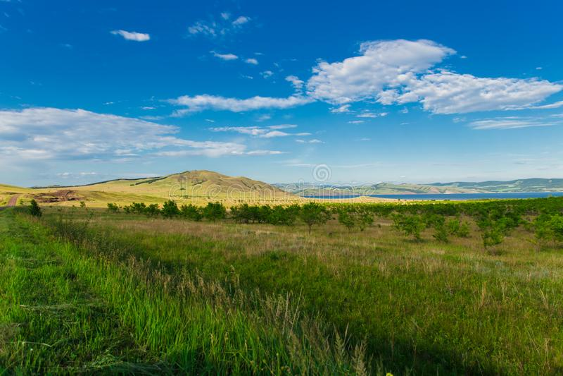 Céu azul com nuvens, as árvores, campos e os prados brancos com grama verde, contra as montanhas Composi??o da natureza imagens de stock royalty free