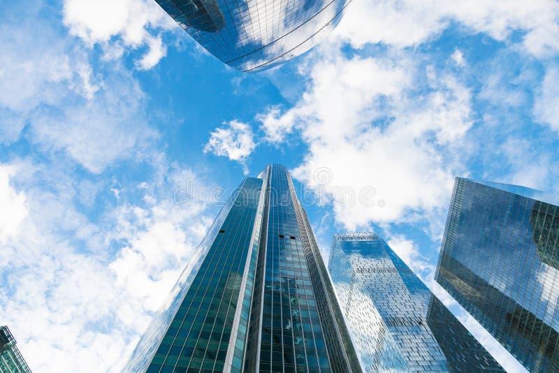 Céu azul com nuvens e partes superiores dos arranha-céus de vidro foto de stock