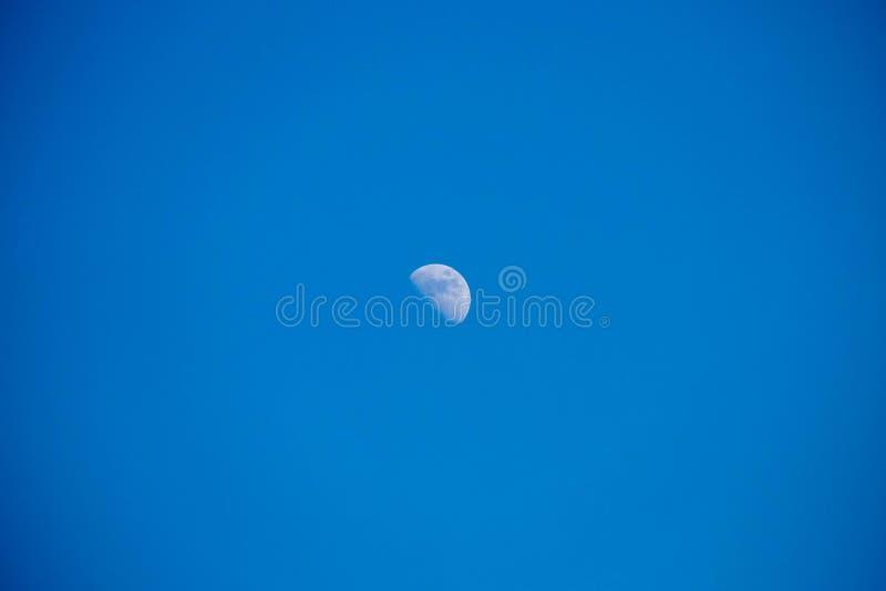 Céu azul da lua na claro durante um dia foto de stock