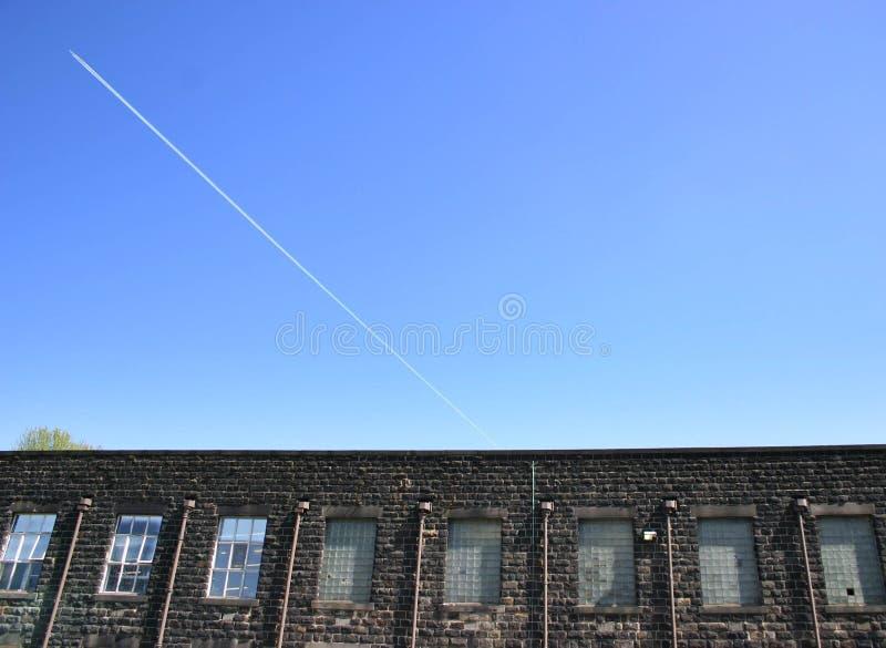 Céu azul das janelas das fábricas e um plano foto de stock royalty free