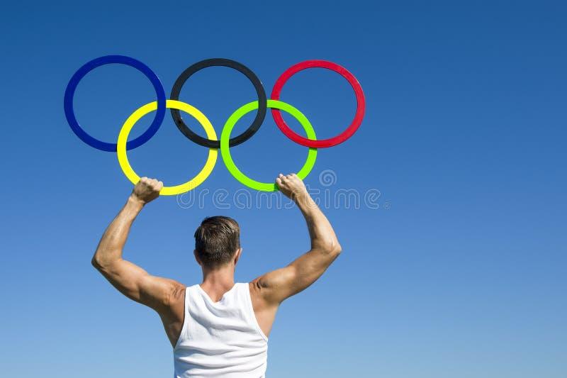 Céu azul de Holds Olympic Rings do atleta foto de stock royalty free