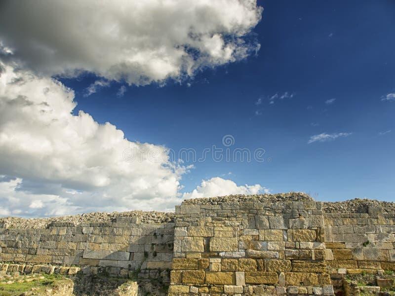 Céu azul dramático com as nuvens brancas sobre as ruínas da colônia do grego clássico de Histria, nas costas do Mar Negro Histria imagens de stock
