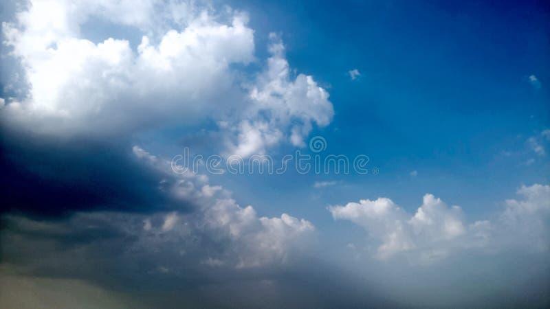 Céu azul e nuvens brancas & pretas inchado imagem de stock