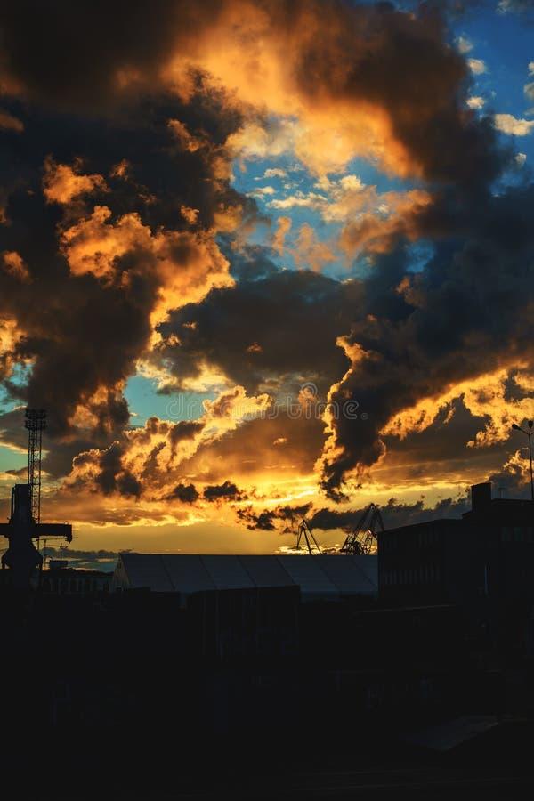 C?u azul fant?stico com as nuvens alaranjadas durante o por do sol ?rea de porto Paisagem fotos de stock royalty free