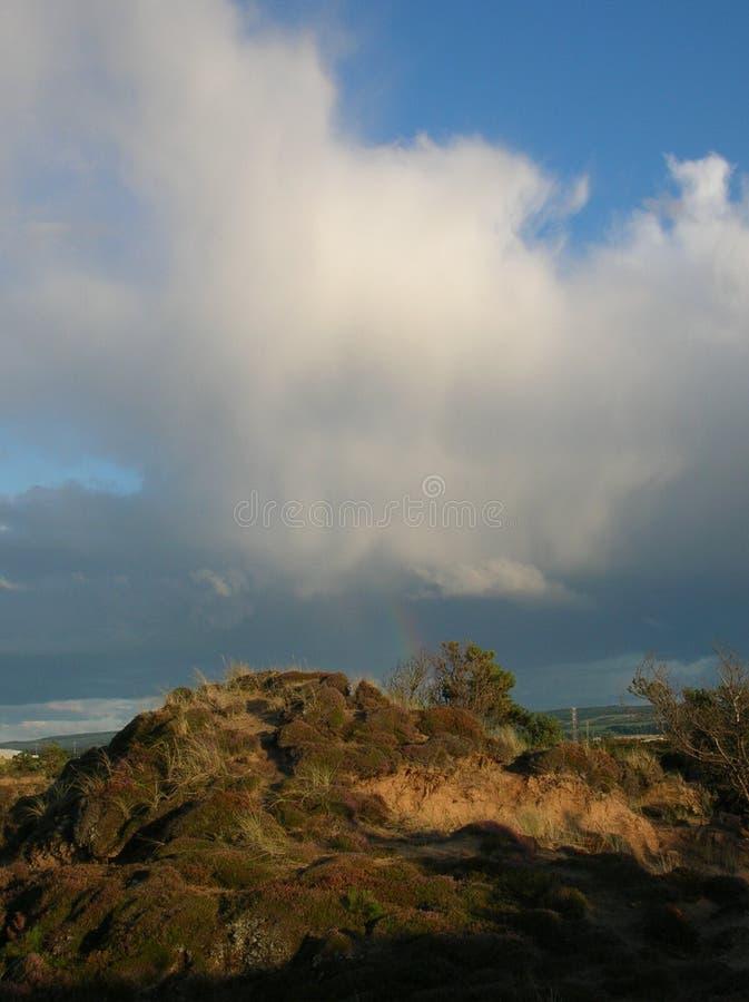 Céu azul fascinante com descarregamento dos nuvems tempestuosa e um arco-íris sobre dunas da baía de Findhorn, Escócia foto de stock