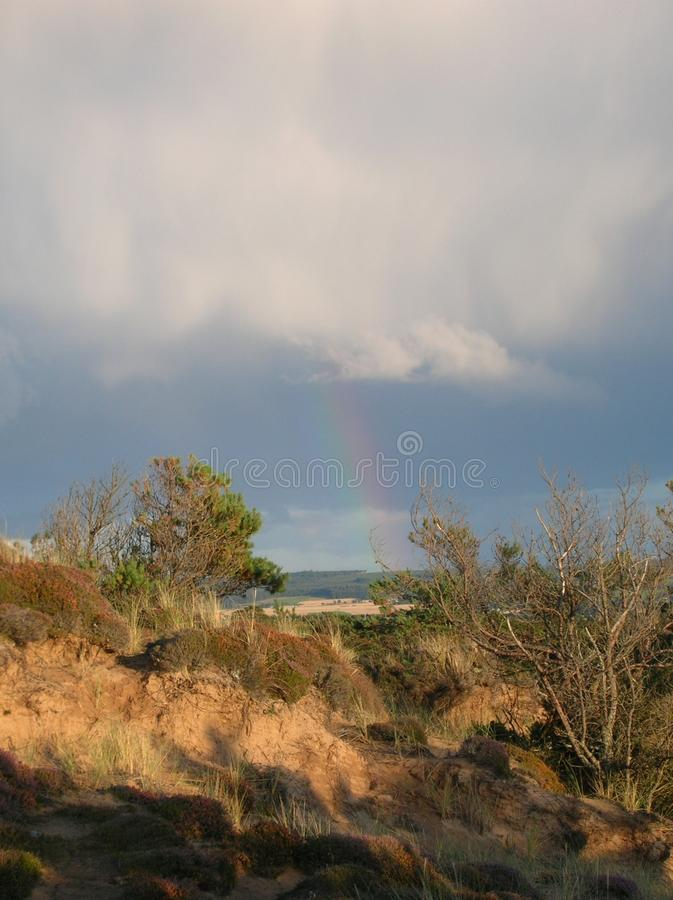 Céu azul fascinante com descarregamento dos nuvems tempestuosa e um arco-íris sobre dunas da baía de Findhorn, Escócia fotos de stock royalty free