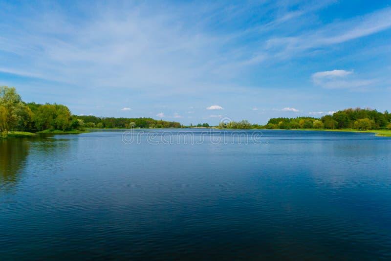 Céu azul sobre o lago azul cercado por madeiras verdes Cenário do verão imagem de stock
